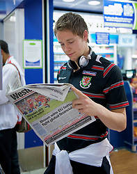 CARDIFF, WALES - Monday, October 13, 2008: Wales' Chris Gunter checks out the match report in the Western Mail newspaper as the team depart from Cardiff Airport ahead of the 2010 FIFA World Cup South Africa Qualifying Group 4 match against Germany. (Photo by David Rawcliffe/Propaganda)