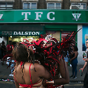 Two women checking up on their lipstick. Hackney carnival 2016 took place on a hot Indian summer's day, September 2016 with the streets full of partying people.
