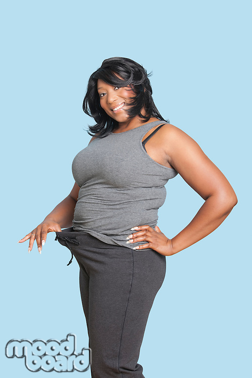 Portrait of mixed race woman pulling put her loose pants waistline over blue background