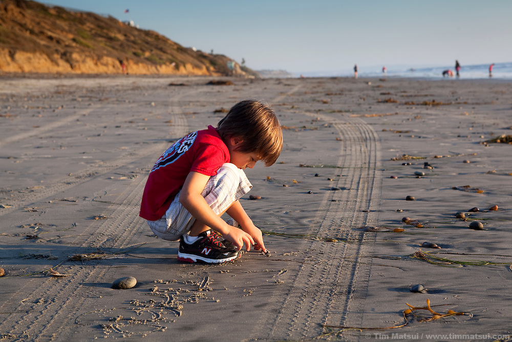A young boy age five (5) plays in the sand at a California beach late in the afternoon.