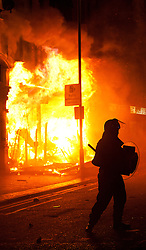 © Licensed to London News Pictures. 09/08/2011 LONDON, UK. Police stand in front of a burning shop on London Road in Croyden after it was set alight by rioters. The fire took place as Croydon was hit during a third night of violence across London which also spread to at least three other cities in the United Kingdom. Photo credit: Matt Cetti-Roberts/LNP