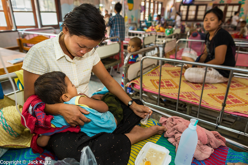 05 MARCH 2014 - MAE SOT, TAK, THAILAND: A woman feeds her baby in the pediatrics ward at the Mae Tao Clinic. The child came to the clinic with a skin infection. The Mae Tao Clinic provides healthcare to over 150,000 displaced Burmese per year and is the leading healthcare provider for Burmese along the Thai-Myanmar border. Reforms in Myanmar have alllowed NGOs to operate in Myanmar, as a result many NGOs are shifting resources to operations to Myanmar, leaving Burmese migrants and refugees in Thailand vulnerable.     PHOTO BY JACK KURTZ