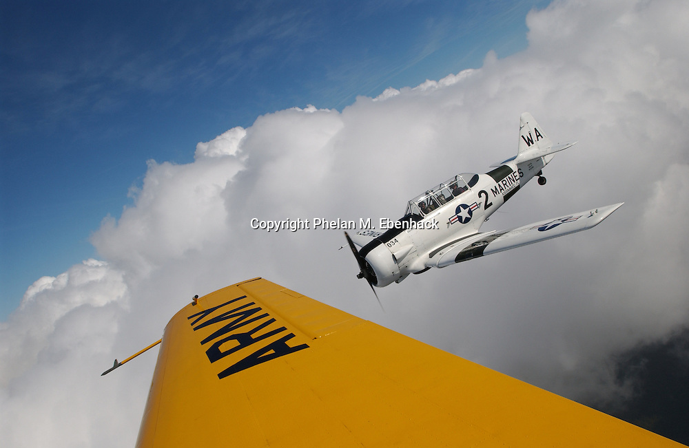 A Marines SNJ-6 Texan WW-II era advanced trainer flies through the clounds over Osceola County, Florida.