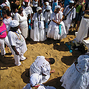 Religious participants of the Candomblé religion, engaging in traditional song, dance, and prayers, take to the beaches of the neighborhood of Rio Vermelho, in Salvador, Brazil in celebrationg of the Festa de Iemanjá, or Festival of Yemayá. The festival is a celebration of the Candomblé deity, or orixás, Iemenjá, who is a goddess of the sea and embodies the feminine principle.  The religious bring offerings to Iemenjá, which are sent out to sea and dropped in the water by boats waiting on the shore for this purpose. It is believed that offerings which are not returned to shore by the sea over the following days are deemed accepted by Iemenjá. Photo by Jen Klewitz