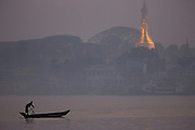 Man rowing boat in early morning mist with Pagoda and city in background, Pathein