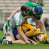 Clare's Aaron Cunningham gets fouled by  Limerick's goalie Nickie Quaid and Sean Finn