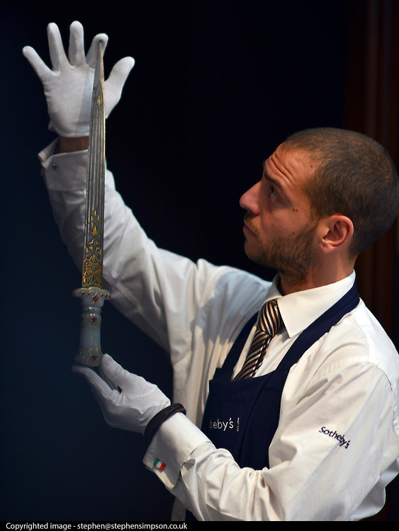 """© Licensed to London News Pictures. 28/09/2012. London, UK A member of auction room staff holds a 18th century Mughal gem set jade hilted dagger. It is expected to raise 40,000-50,000GBP. Sotheby's Auction rooms in New Bond Street, London hold a photo call for their upcoming """"arts of the Islamic World"""" auction which is expected to realise in the region of 5 million GBP . Photo credit : Stephen Simpson/LNP"""