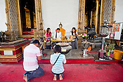 08 OCTOBER 2009 -- BANGKOK, THAILAND: People pray in front of the ordination hall at Wat Suthat. Wat Suthat, in Bangkok, Thailand, is one of the most important Buddhist temples in Thailand. Parts of it were made Thai King Rama II. It features both the largest odination hall and largest main chapel of any Buddhist temple in Thailand.   Photo By Jack Kurtz
