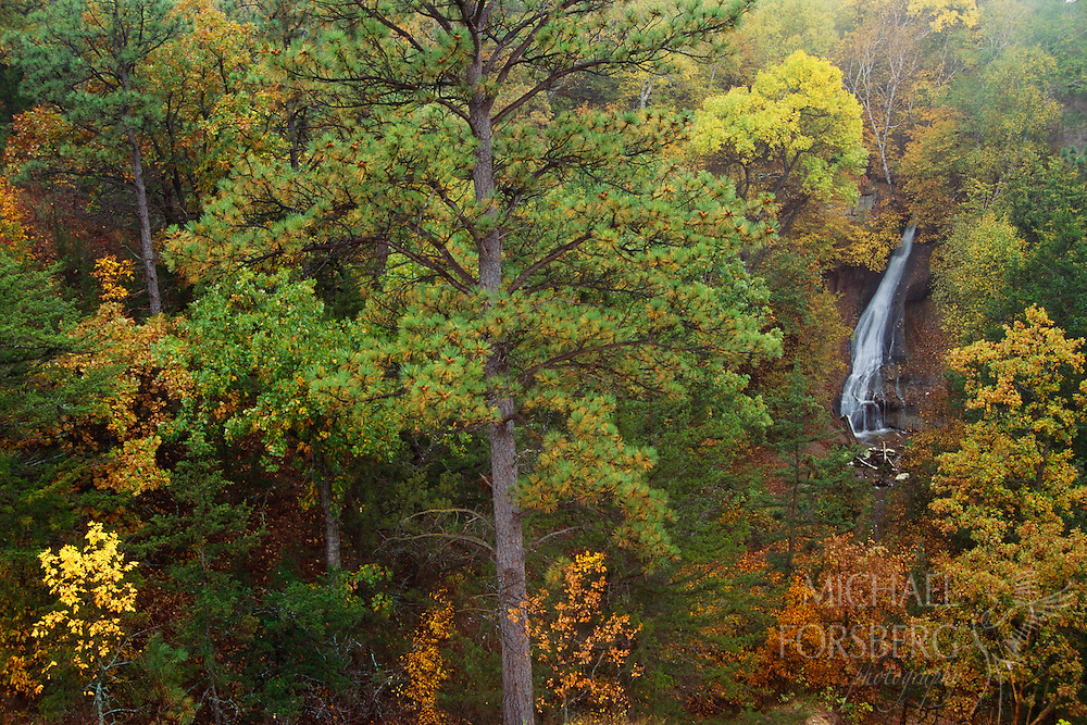A waterfall in the Niobrara River Valley divides trees starting to show their fall colors.  Fort Niobrara National Wildlife Refuge, Nebraska.
