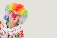 Happy senior clown looking up against gray background