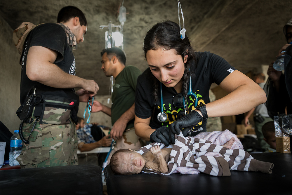 A critically malnourished two-month-old baby is examined by frontline paramedic Katie Batrouney at a makeshift field clinic on the edge of Mosul's Old City, Iraq, on June 21, 2017.<br />