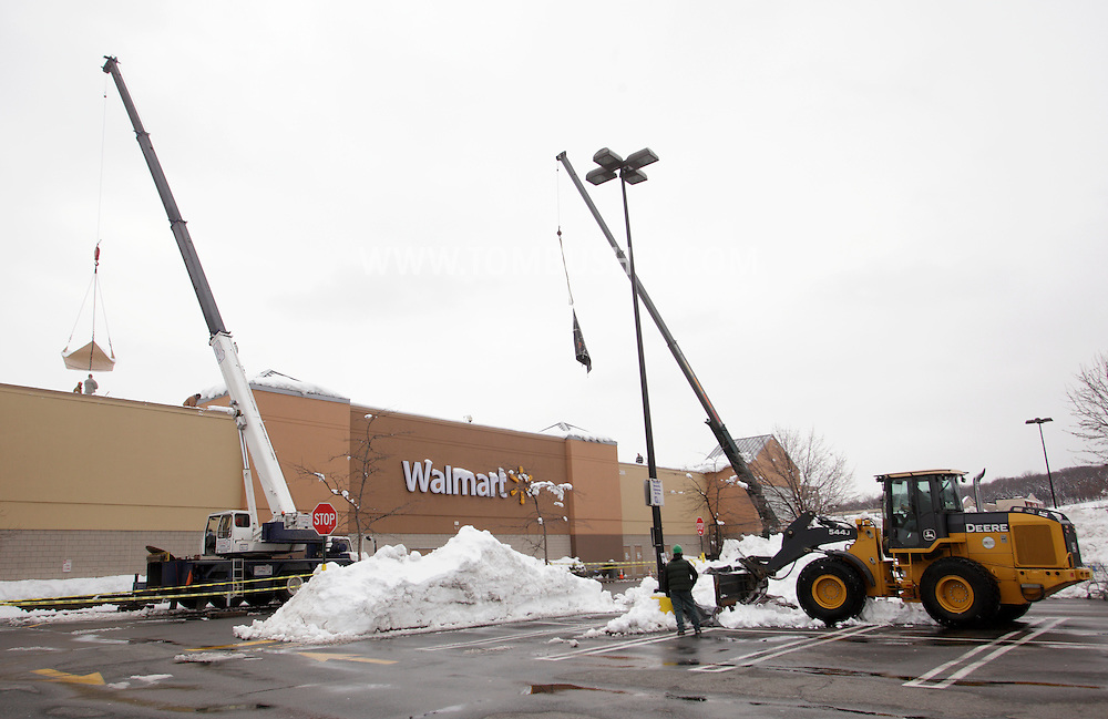 Harriman, New York - A crane, at left, lifts a tarp full of snow off the roof of the Walmart store as a front end loader works in the parking lot after than 30 inches of snow fell after a storm on Feb. 27, 2010. The store remained closed until the snow was removed and the roof was inspected.