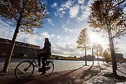 In Haarlem rijdt een fietser op het fietspad langs de Spaarne.<br /> <br /> In Haarlem a cyclist in a bike lane passes the Spaarne.