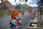 In Ban Phan Luang, across the Nam Khan River from Luang Prabang, Laos. Every morning at dawn, Buddhist monks walk down the streets collecting food alms from devout, kneeling Buddhists, and some tourists. They then return to their temples (also known as wats) and eat together. This procession is called Tak Bat, or Making Merit.
