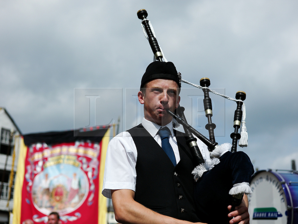 """© Licensed to London News Pictures. 13/07/2013<br /> <br /> Durham City, England, United Kingdom<br /> <br /> A piper plays as part of a colliery band during the Durham Miners Gala.<br /> <br /> The Durham Miners' Gala is a large annual gathering held each year in the city of Durham. It is associated with the coal mining heritage of the Durham Coalfield, which stretched throughout the traditional County of Durham, and also gives voice to miners' trade unionism. <br /> <br /> Locally called """"The Big Meeting"""" or """"Durham Big Meeting"""" it consists of banners, each typically accompanied by a brass band, which are marched to the old Racecourse, where political speeches are delivered. In the afternoon a Miners' service is held in Durham Cathedral <br /> <br /> Photo credit : Ian Forsyth/LNP"""