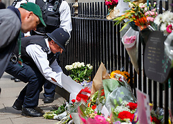 © Licensed to London News Pictures. 07/07/2015. London, UK. Police officers pay their respects to 7/7 London bombings victims on the 10th anniversary of 7/7 London bombings in Tavistock Square on Tuesday, July 7, 2015. Photo credit: Tolga Akmen/LNP