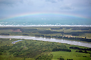 A rainbow graces Oreti Beach, with the Oreti River arcing through the green coastal pastures in Invercargill, Southland