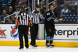 April 16, 2012; San Jose, CA, USA; San Jose Sharks center Andrew Desjardins (69) is escorted to the penalty box by NHL linesman Jean Morin (97) and referee Paul Devorski (10) during the third period of game three of the 2012 Western Conference quarterfinals against the St. Louis Blues at HP Pavilion.  St. Louis defeated San Jose 4-3. Mandatory Credit: Jason O. Watson-US PRESSWIRE