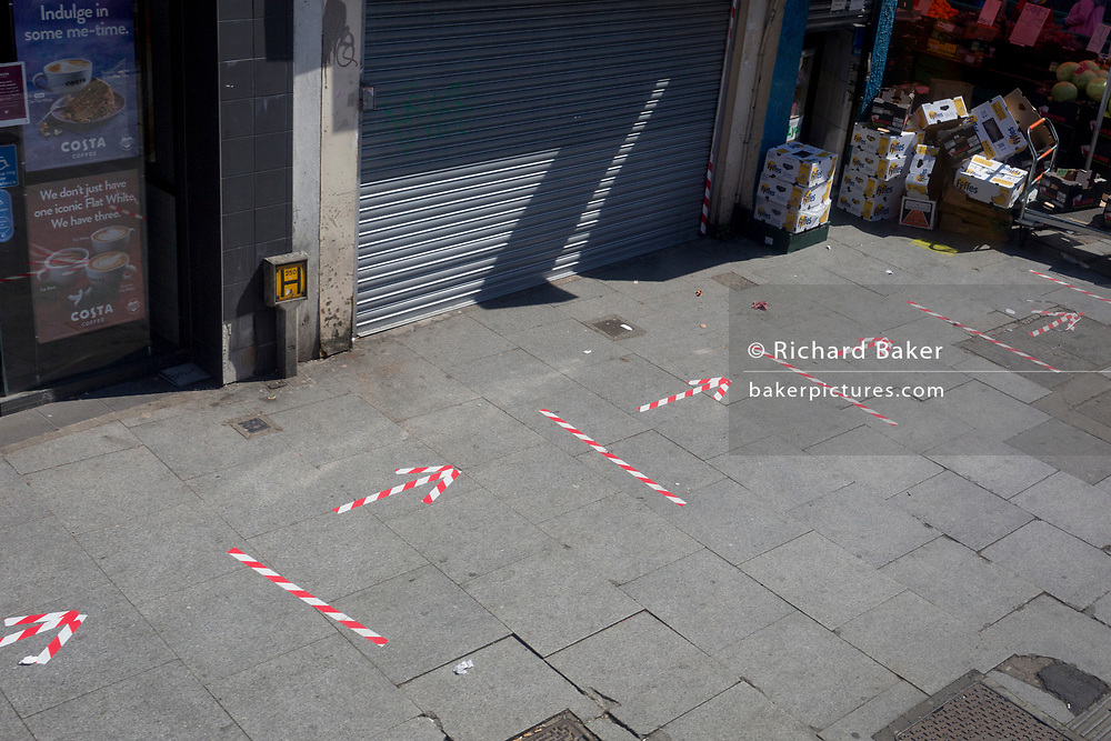 As the UK government's Coronavirus pandemic lockdown continues, and <br /> a further 823 people have died in hospitals across the UK in a day, taking the total to 17,337, hazard tape stuck to the pavement diagonally marks social distancing areas and directions for queuing shoppers visiting East Street Market on the Walworth Road near Camberwell, on 21st April 2020, in London, England.
