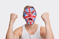 Portrait of happy young Caucasian man with British flag painted on face celebrating success against white background
