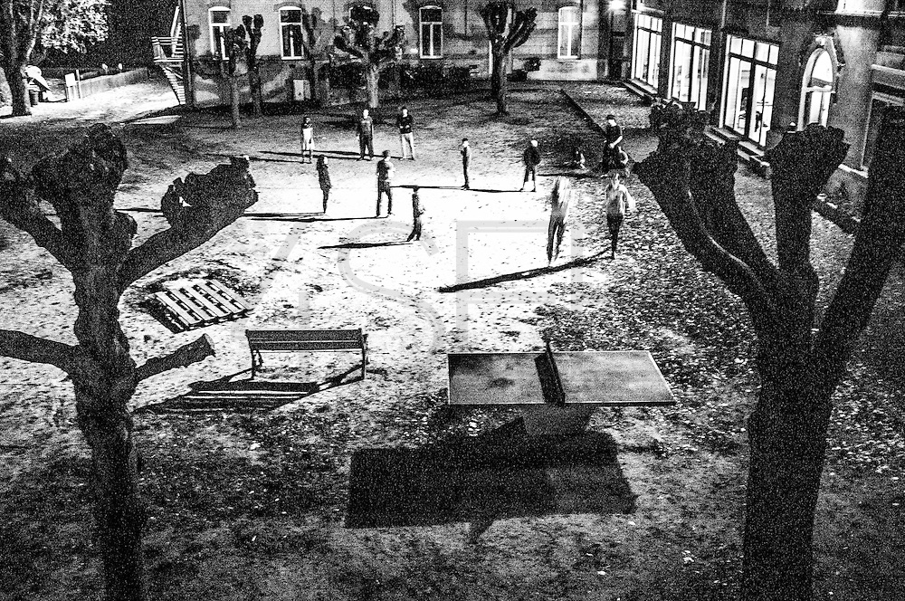 A group of residents and international volunteers are playing games on the backyard playground of the center at night. FEDASIL Rixensart asylum center. Rixensart, Belgium. April 2015. I took these photographs during an international volunteer program that I liderate with an international volunteering group.