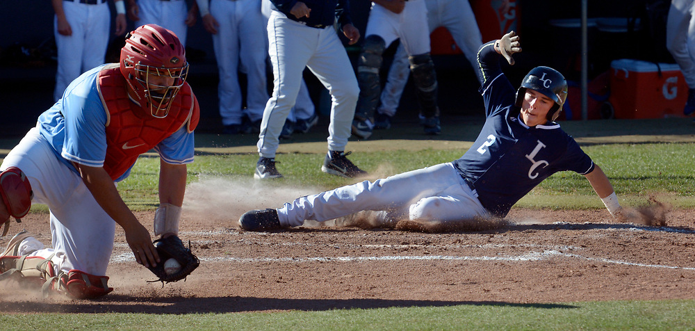 gbs031417k/SPORTS -- La Cueva's Jack Pineda, 2, slides home safely as Sandia Catcher Chris Hamilton gets the throw away from home plate in the 2nd inning of the game at La Cueva on Tuesday, March 14, 2017. (Greg Sorber/Albuquerque Journal)
