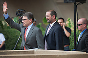 Texas Gov. Rick Perry leaves the Dallas/Fort Worth Stands by Israel rally followed closely by advisor Jeff Miller on Wednesday July 30, 2014 at Dallas City Hall in Dallas, Texas.