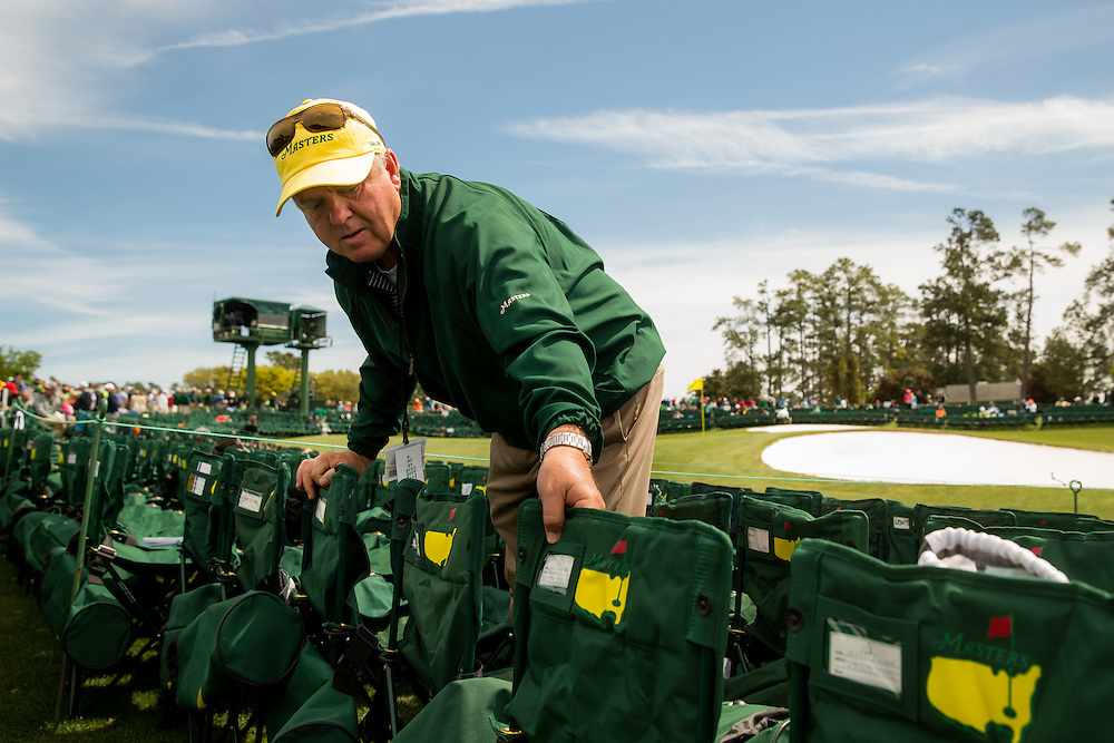 Gallery guard John Gibson, who has been assisting the patrons at the 18th green for 22 years, tries to make room for one more chair.Golf: 2016 Masters<br /> Round 4 Sunday<br /> Augusta National/Augusta, GA, USA<br /> 04/10/2016<br /> SI-14 TK4<br /> Credit: Darren Carroll
