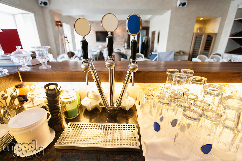 Beer taps and glasses at bar counter