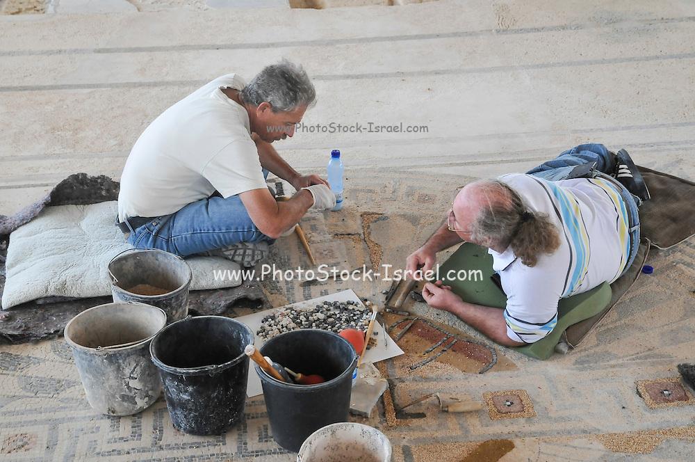 Archeologists restore a mosaic floor in Caesarea, Israel