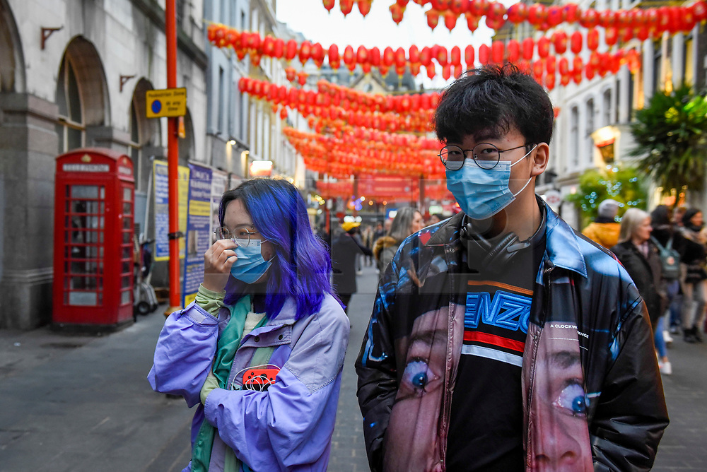 © Licensed to London News Pictures. 24/01/2020. LONDON, UK. A couple wear facemasks, possibly in reaction to the outbreak of the coronavirus in Wuhan, China as red lanterns decorate Chinatown ahead of Chinese New Year, the Year of the Rat.   Photo credit: Stephen Chung/LNP