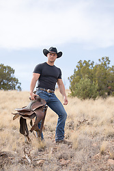 hot rugged cowboy holding a saddle outdoors