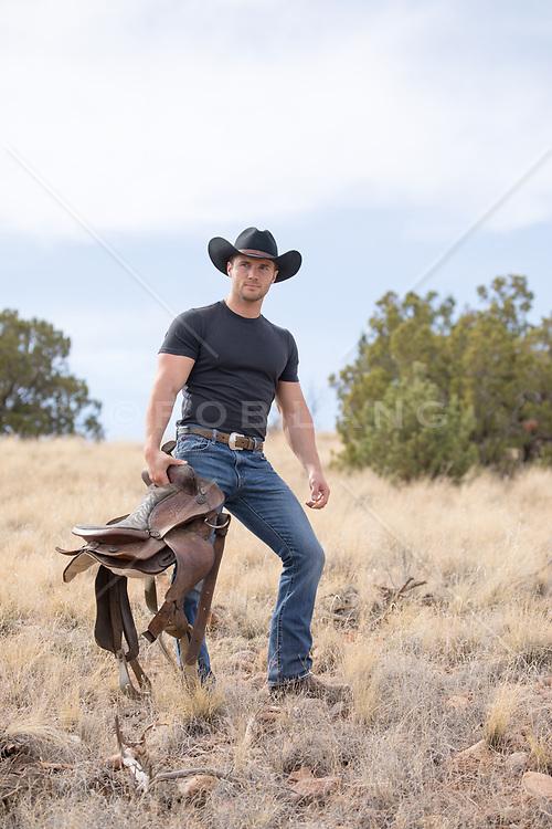 hot rugged cowboy holding a saddle outdoors