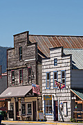 Old wooden buildings in the tiny village of Petersburg on Mitkof Island along the Wrangell Narrows in Frederick Sound with the Alaska Coast Range of mountains behind on Mitkof Island, Alaska. Petersburg settled by Norwegian immigrant Peter Buschmann is known as Little Norway due to the high percentage of people of Scandinavian origin.