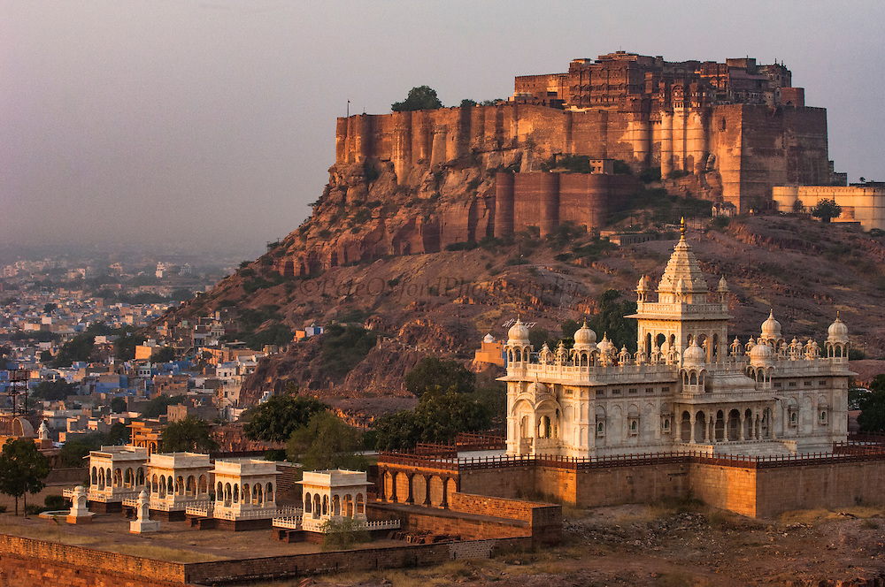 Mehrangarh Fort of Jodhpur and Jaswant Thada in the foreground. Rajasthan, INDIA<br /> This is one of the most impressive fortresses in rajasthan. Perched on top of a rocky cliff 400 feet above the plain, it has a commanding view of the surrounding area. The fort itself is divided broadly into 3 areas: the outer court, with its old stables and kitchens, the Durbar hall, reception rooms and maharajas palaces and finally the zenana, or queen's palaces. The palace complex constructed around a series of interconnecting courtyards and adorned with breathtaking carved sandstone filigree was first built in 1459 and added to over the centuries. <br /> The Jaswant Thada is a graceful marble cenotaph (tomb) of Maharaja Jaswant Singh II (reigned 1873-95) and those of the other Maharajas who died in this century.<br /> The Kingdom of Jodhpur was established in the 12th century but in the 15th century the fort and city walls were constructed and they still stand today. Jodhpur is the second largest city in Rajasthan with a population of 1.3 million. Jodhpur may be called the 'Blue City' from the characteristic pale indigo colour of its traditional homes. Originally the color signified the home of the Jodhpuri Brahmin but the copper sulphate in the paint seems to ward off termites and mosquitos so many people then followed the traditional of painting their homes blue. The very narrow streets are filled with colourful bazaars where merchants are selling their wares.