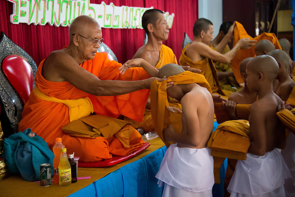 Young men, with the help of older monks begin to put on the robes of a monk in rural Nakhon Nayok, Thailand.