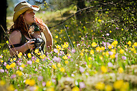 Jessi Zichko sits on a hillside covered in wildflowers while surveying the landscape for a photo opportunity while out with her North Idaho College photography class Monday on Tubbs Hill.