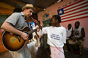 A young Liberian girl from the Liberian Dance Troupe (LDT) holds up the microphone for Canadian artist Dave Bidini to sing during a performance at the Buduburam refugee settlement, roughly 20 km west of Accra, Ghana's capital, on Saturday April 14, 2007. One of the main goals of the LDT is to teach young refugee children, many of which have never seen Liberia, about their country's music, dance and culture. The Buduburam refugee settlement is still home over 30,000 Liberians, most of which have mixed feelings about returning to Liberia..