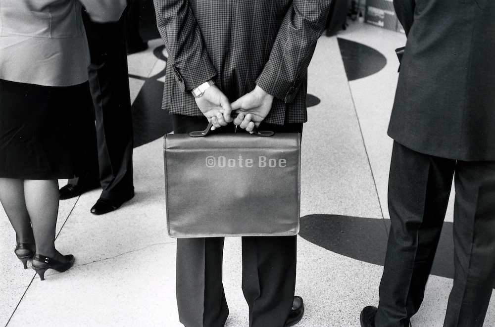 Business man holding his brief case behind him