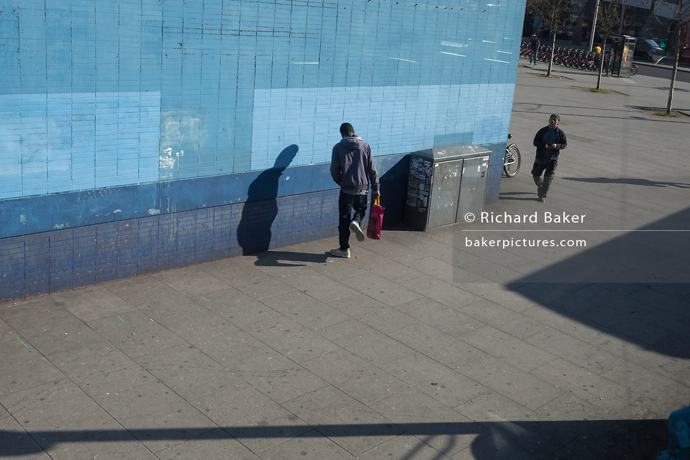 A man acts strangely while facing a blue wall at Elephant & Castle in Southwark, on 26th February, in London, England.