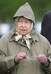 The Queen shelters from the rain in a raincoat and a hood at the Royal Windsor Horse Show, Friday, May 10th 2013.  Photo by: Stephen Lock / i-Images