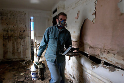 21 December 05. New Orleans, Louisiana. Post Katrina aftermath.<br /> 20 yr old Tristan Devezin clears his grandfathers' devastated, mould filled house in the 9th Ward long after the  flood from Hurricane Katrina subsided. The house has only recently been refurbished and has seen water to the ceilings before when Hurricane Betsy hit in the 1960's.<br /> Photo; ©Charlie Varley/varleypix.com