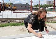 Grady Middle School Principal Gretchen Kasper-Hoffman signs a beam on Monday, May 5, 2015, in celebration of vertical construction on the school's new classroom wing.