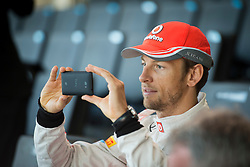 © London News Pictures. 31/01/2013 . Woking, UK.  Team McLaren Mercedes  driver Jenson Button using his mobile phone to photograph  the new MP4-28 Formula 1 car at its unveiling at the McLaren Technology Centre in Woking, Surrey, UK on  Thursday, Jan. 31, 2013. Photo credit : Ben Cawthra/LNP