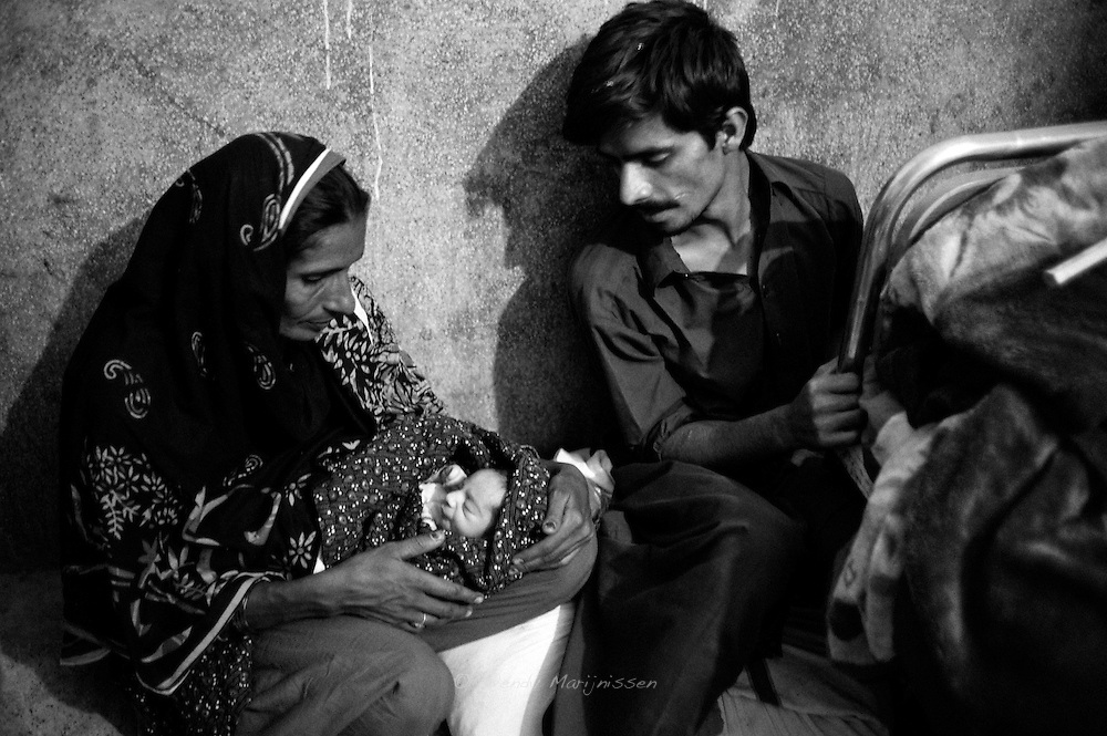 Makhoul and his mother sit by the end of Rabia's bed, talking and looking in wonder at the new member of their family. Thari Mirwah, Pakistan, 2010