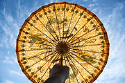 old style Asian paper umbrella hold up against the sun with a blue sky