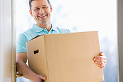 Happy man carrying cardboard box at entrance of new house