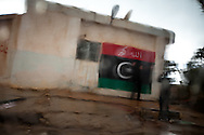 Youths photograph each other in front of a newly painted Free Libya flag in Benghazi on March 1, 2011.