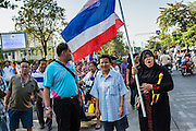 "01 FEBRUARY 2014 - BANGKOK, THAILAND: A Thai Muslim woman carries a Thai flag to confront anti-government protestors that were preventing her from voting. She wanted to vote and was upset when protestors shut her polling place. Thais went to the polls in a ""snap election"" Sunday called in December after Prime Minister Yingluck Shinawatra dissolved the parliament in the face of large anti-government protests in Bangkok. The anti-government opposition, led by the People's Democratic Reform Committee (PDRC), called for a boycott of the election and threatened to disrupt voting. Many polling places in Bangkok were closed by protestors who blocked access to the polls or distribution of ballots. The result of the election are likely to be contested in the Thai Constitutional Court and may be invalidated because there won't be quorum in the Thai parliament.    PHOTO BY JACK KURTZ"