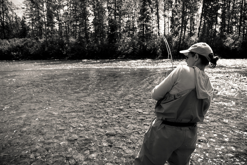 Angler Denise Rogers fighting a fly caught king salmon in the East Fork of the Chulitna River, Alaska